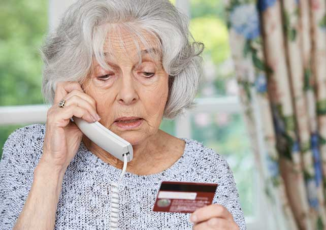 Grandmother on phone holding credit card