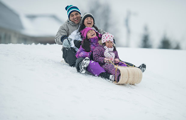 Family tobogganing down hill